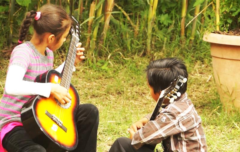 Una niña enseña a otro niño a tocar la guitarra. (Foto Prensa Libre: Josué León)