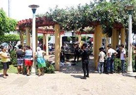Agentes de la Policía Nacional Civil protegen la escena en que falleció un hombre en el parque central de Ratalhuleu. (Foto Prensa Libre: Rolando Miranda)