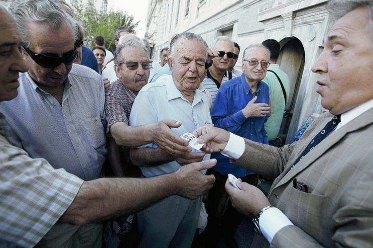 Un empleado reparte turnos  frente a una sucursal del Banco Nacional de Grecia en  Atenas. (Foto Prensa Libre:EFE)