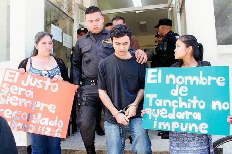 Dos mujeres sostienen dos carteles que recuerdan a la víctima. Sale del juzgado Jonathan Widmar Berreondo, uno de los dos acusados, en Santa Cruz del Quiché. (Foto Prensa Libre: Óscar Figueroa)