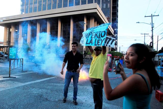 Ciudadanos queman cohetillos  antes de que el bus de los implicados abandone la CSJ. (Foto Prensa LIbre: Edwin Bercián)