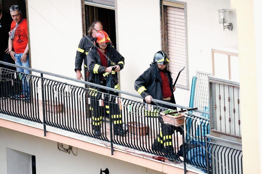 Socorristas y policías inspeccionan el balcón desde donde el desequilibrado mató a cuatro en Nápoles, Italia. (Foto Prensa Libre: EFE).