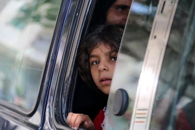 Un niño sirio observa desde la ventana de un vehículo. (Foto Prensa Libre: AFP).