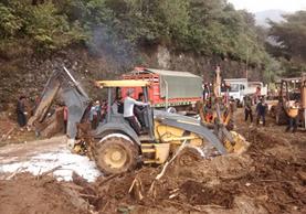 Un tractor trata de despejar la ruta donde ocurrió la tragedia en San Pedro Soloma, Huehuetenango. (Foto Prensa Libre: Mike Castillo)