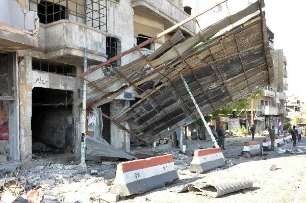 Soldados del ejército sirio inspección los daños causados por un carro bomba en Homs.
