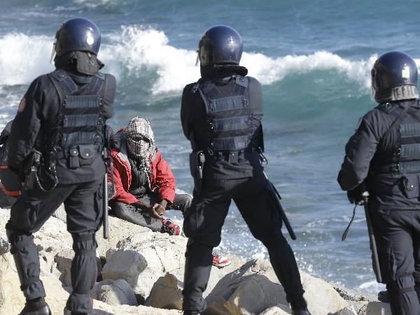 Un emigrante escucha a grupo de policías italianos ttras surescate. (AP).