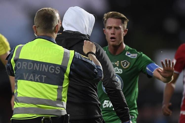 Un aficionado es detenido por los miembros de seguridad después de agredir al portero Aly Keita durante el partido de la liga de futbol sueca entre Jonkoping y Ostersund.
