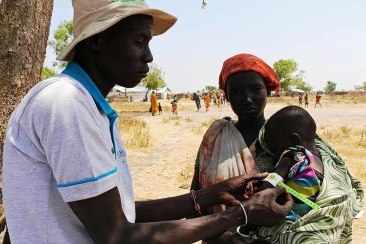 Un trabajador sanitario evalúa a una madre y su pequeño hijo, afectados por la hambruna. (Foto Prensa Libre: AFP).