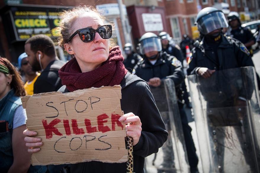 """""""Alto policías asesinos"""", se lee en este cartel que porta una manifetante. (Foto Prensa Libre: AFP)."""