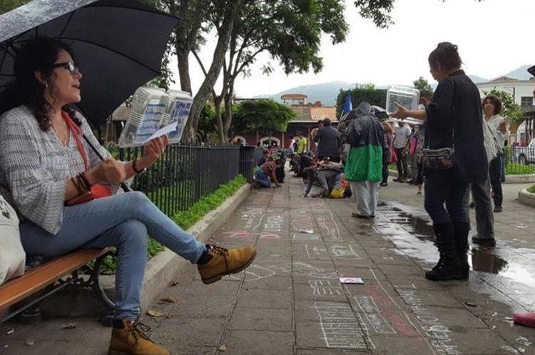 Personas dibujan con tiza en el piso del parque central para simular unos estantes con libros (Foto Prensa Libre: Julio Sicán).