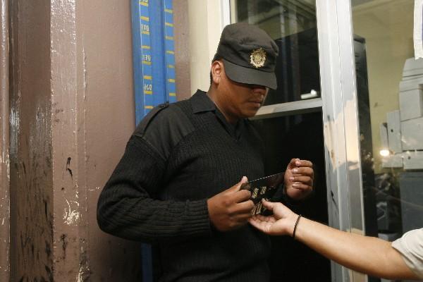 El agente Efraín Nicolás  es fichado, después de su detención, sindicado de haber extorsionado  a piloto de  camión de valores.