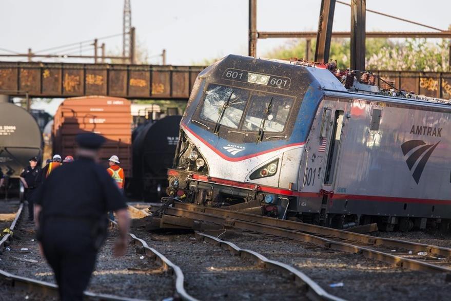 Oficiales vigilan el área donde se accidentó el tren, percance que dejó al menos 7 muertos. (Foto Prensa Libre: EFE).