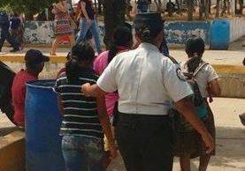 Una agente de la PNC custodia a las tres menores rescatadas. (Foto Prensa Libre: PNC).