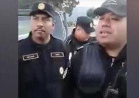 El agente señalado -izquierda- podría ser sancionado por la seña obscena. (Foto Prensa Libre: tomada del video)