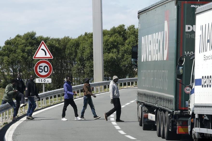 Inmigrantes cruzan una carretera cerca de la entrada del Eurotúnel, en Coquelles, cerca de Calais, Francia. (Foto Prensa Libre: EFE).