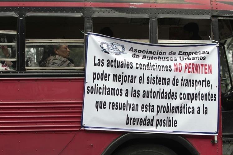Buses de transporte urbano circulan con mantas en las que se exige el pago del subsidio de parte del Gobierno. (Foto Prensa Libre: Erick Ávila)