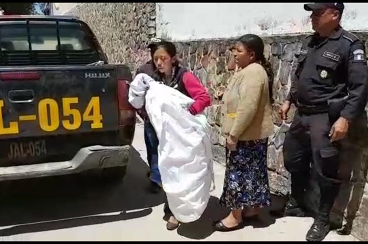 La madre del bebé, Adela Cruz, lo carga en brazos al salir de la funeraria en la cabecera de Jalapa. (Foto Prensa Libre: Hugo Oliva)