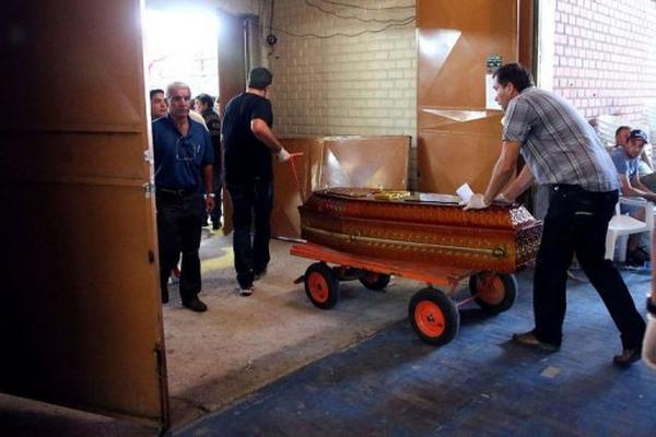 <p>Empleados de una funeraria trasladan un ataúd este lunes en Santa María, al sur de Brasil. (AFP).<br></p>