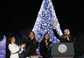 Barack Obama acopmañado de Michelle Obama (2 ª izquierda) y su hija Sasha (c)encienden el árbol de Navidad. (AFP).