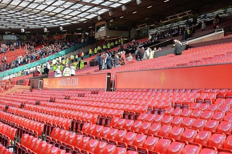 Seguidores del Manchester United abandonan el estadio después de escuchar que se suspendió por medidas de seguridad. (Foto Prensa Libre: EFE)