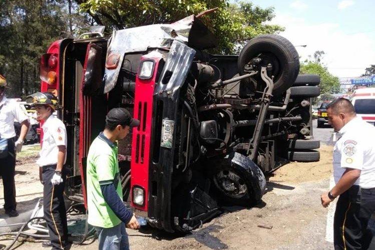 Bomberos permanecen en el lugar donde volcó el autobús. (Foto Prensa Libre: Cruz Roja)