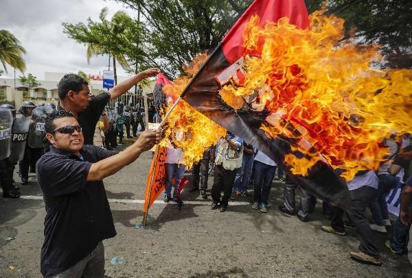 """<em><span class=""""hps"""">Un activista</span><span class=""""hps""""> quema</span> <span class=""""hps"""">una bandera</span> <span class=""""hps"""">sandinista</span> <span class=""""hps"""">durante una protesta</span><span class=""""hps""""> en</span> <span class=""""hps"""">Managua</span><span>.(Foto Prensa LIbre:AFP).</span></em>"""