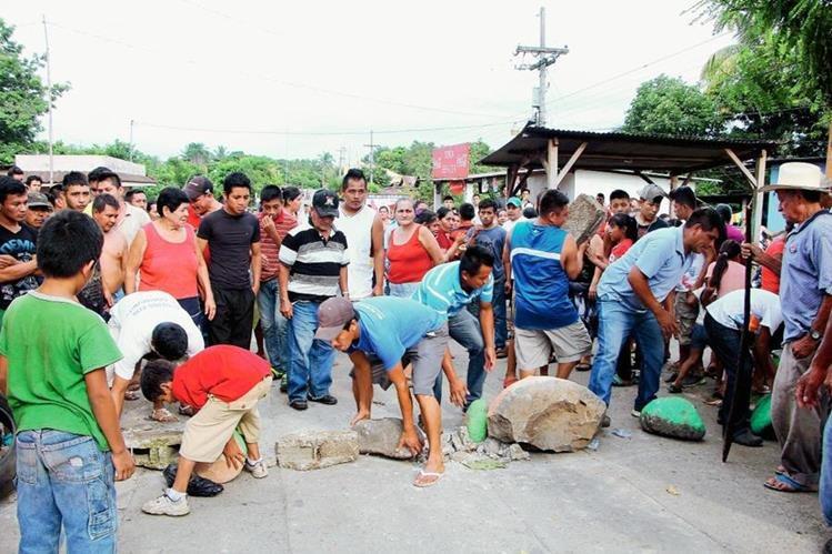 Pobladores de Santa Cruz Muluá, Retalhuleu, bloquean el paso de vehículo en que se desplazaban  trabajadores del INDE, en presión para que ENERGUATE les arreglara servicio eléctrico. (Foto Prensa Libre: Rolando Miranda)