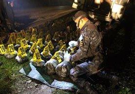 Agentes antinarcóticos de la PNC contabilizan droga incautada en Dolores, Petén. (Foto Prensa Libre: PNC)