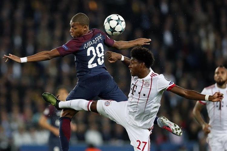 David Alaba del Bayern disputa el balón con Kylian Mbappe del PSG.