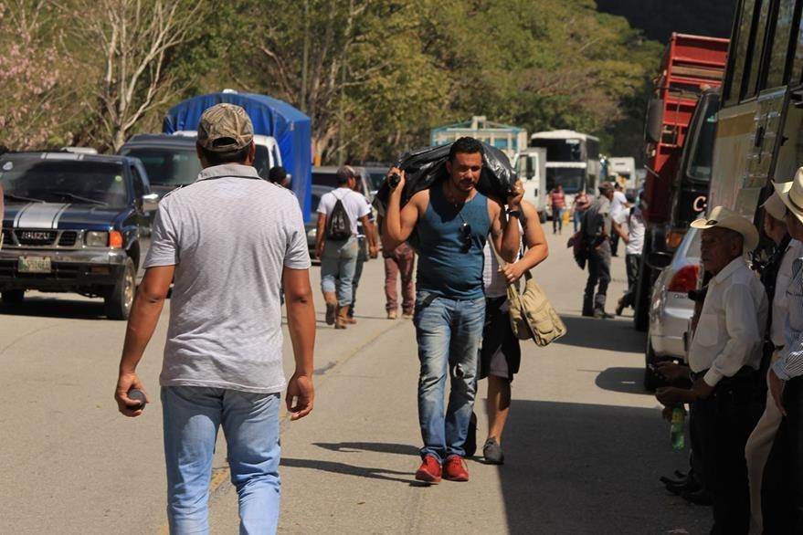 Turista hondureño camina para llegar a su destino, debido al bloqueo en la aldea Machaquilá. (Foto Prensa Libre: Walfredo Obando).