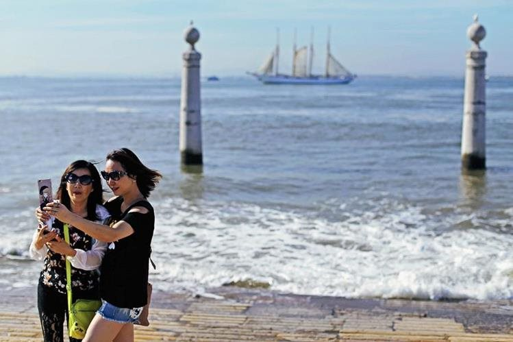 Turistas toman un selfie en el muelle de Cais das Colunas por la orilla del río Tajo, en Lisboa. (Foto Prensa Libre: AP).