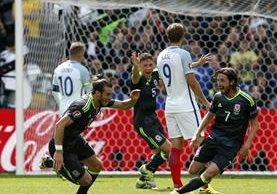 El galés Gareth Bale (izquierda) sonríe y comienza el festejo después de anotar de tiro libre contra Inglaterra. (Foto Prensa Libre: EFE)