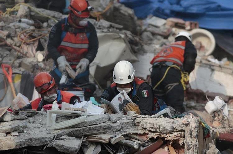 Un brigadista mira un álbum de fotos mientras trabajan en operaciones de rescate.(AP)