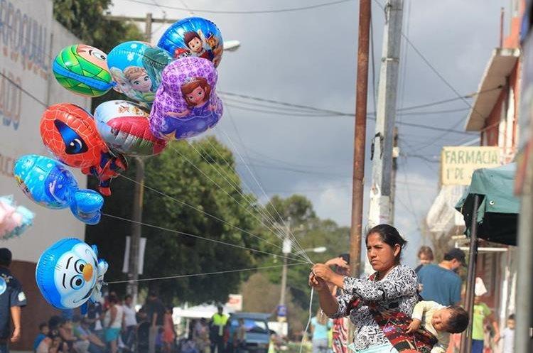 Una vendedora ofrece globos durante los festejos de aniversario de la colonia Primero de Julio.