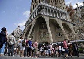Turistas y pobladores tratan de ingresar en la iglesia La Sagrada Familia, que sería atacada por extremistas. (Foto Prensa Libre: EFE)