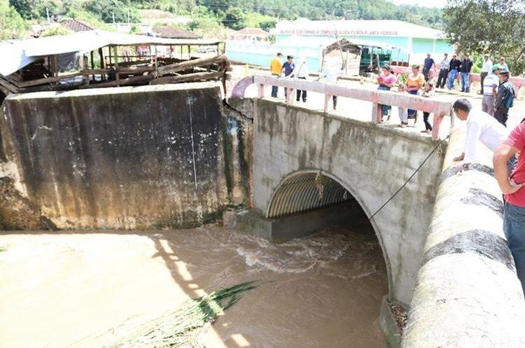 Un grupo de pobladores ven los daños que tiene una parte de la estructura del puente Negro. (Foto Prensa Libre: Héctor Cordero)
