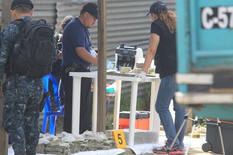 Fiscales y agentes antinarcóticos contabilizan el contenido de los paquetes de billetes de US$20, localizados en dos depósitos de combustible de camión. (Foto Prensa Libre: E. Paredes)