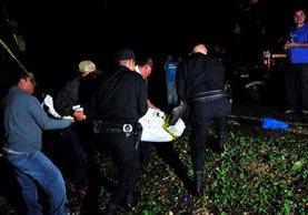 Agentes de la PNC trasladan el cadáver de un maestro que murió por heridas de arma cortante en Sayaxché, Petén. (Foto Prensa Libre: Rigoberto Escobar)