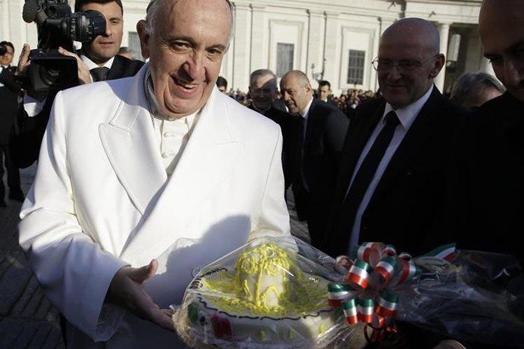 El papa Francisco sostiene un pastel de cumpleaños que recibió un día antes de cumplir 79. (Foto Prensa Libre: AP).