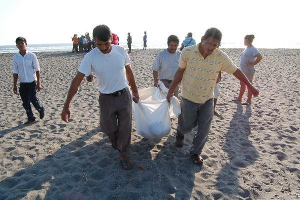 Uno de los cadáveres es retirado de la playa.