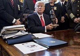 Trump sostiene una figura que le obsequiaron durante una reunión en el Despacho Oval. (Foto Prensa Libre:EFE).
