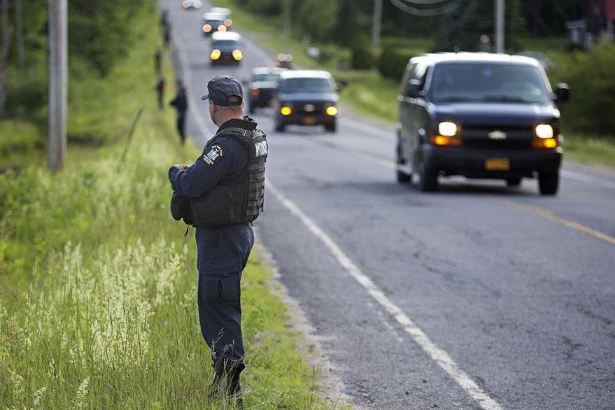 Un guardia de seguridad vigila una carretera en Nueva York, previo a la captura de David Sweat este domingo. (Foto Prensa Libre: AP).