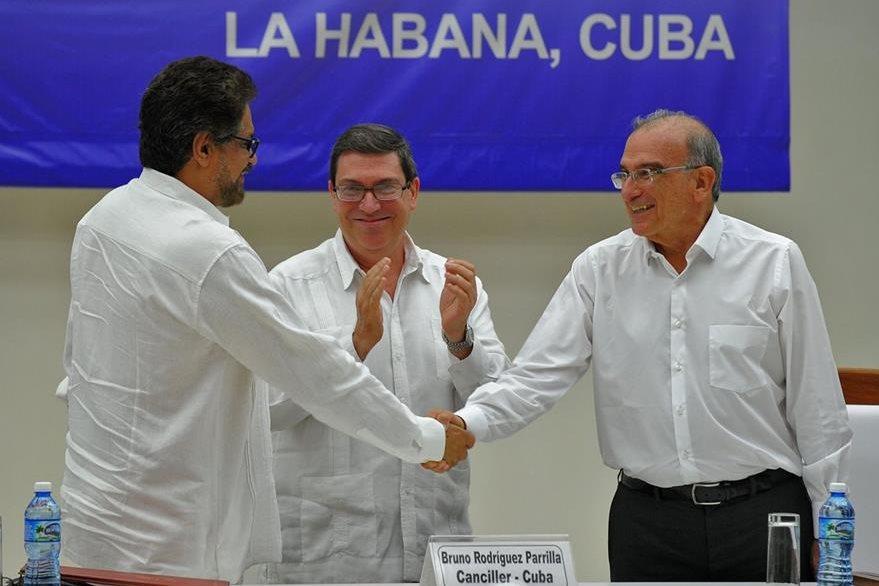 Humberto de la Calle (a la der.) respresentante del Gobierno de Colombia, estrecha la mano del comandante Iván Márquez, de las Farc (a la izq.) luego de la firma del acuerdo en Cuba. (Foto Prensa Libre: AFP).