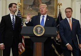 Donald Trump es acompañado por los senadores republicanos Tom Cotton,(d) y a la izquierda David Perdue. (AP).