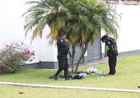 Agentes de la PNC resguardan los cadáveres de dos de las víctimas atacadas a balazos en la calzada Roosevelt. (Foto Prensa Libre: Érick Ávila)