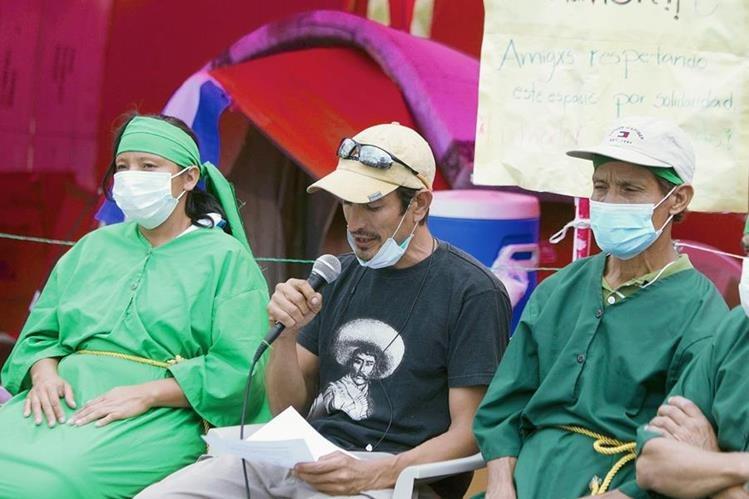 German Ayala (centro) lee el documento en el que aceptan dialogar. (Foto Prensa Libre: EFE).