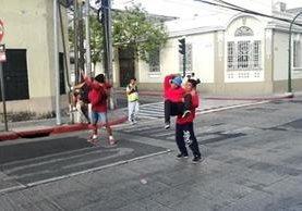 Grupo de bailarines de biboying ejecuta rutina en la 13 calle y 8a. avenida de la zona 1 capitalina, mientras el semáforo marca rojo. (Foto Prensa Libre: Edwin Pitán)