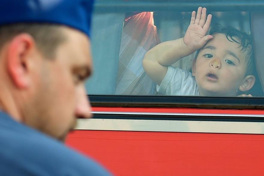 Un niño soporta el sofocante calor en la ventana de un tren que se dirige a a Serbia. (Foto Prensa Libre: AFP).