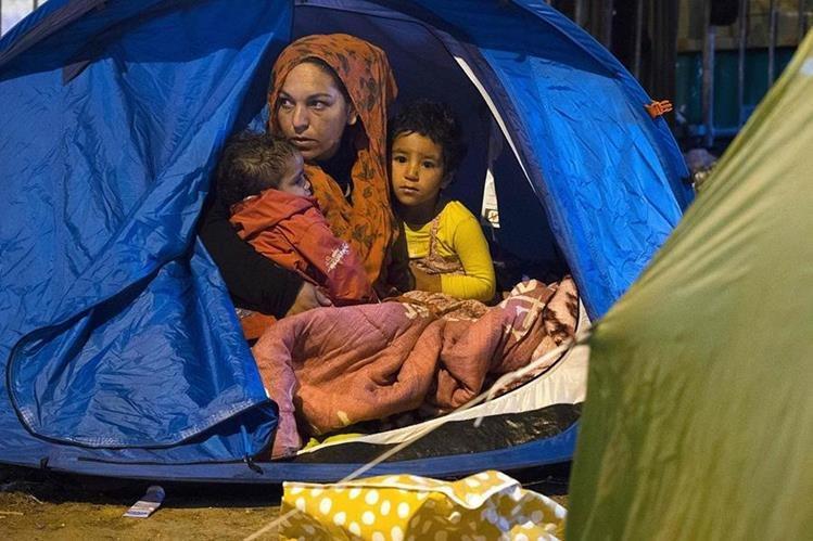 Una familia de migrantes sirios descansa en un campamento improvisado en Calais, Francia, de donde provienen la mayoría de migrantes que llegan a Gran Bretaña. (Foto Prensa Libre: AFP).