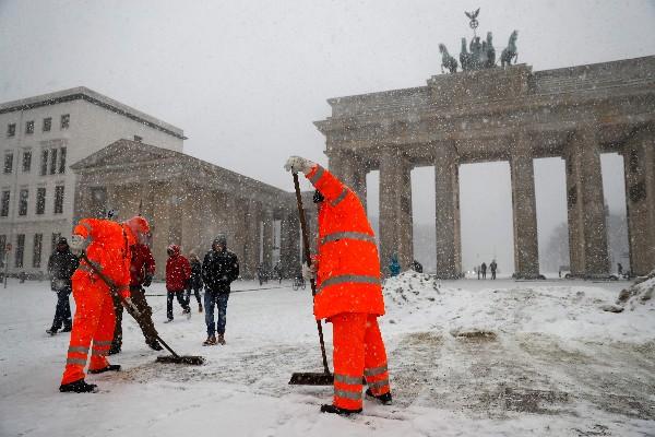 Trabajadores de limpieza quitan la nieve en la puerta de Brandeburgo, Berlín.(AFP).